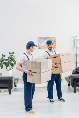 Photo for Two movers in uniform carrying cardboard boxes in apartment with copy space - Royalty Free Image