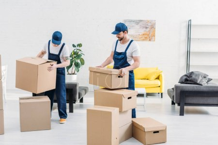 Photo for Two movers in uniform carrying cardboard boxes in modern apartment - Royalty Free Image