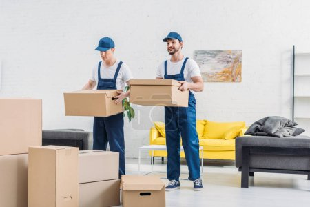 Photo for Two movers transporting cardboard boxes in apartment - Royalty Free Image