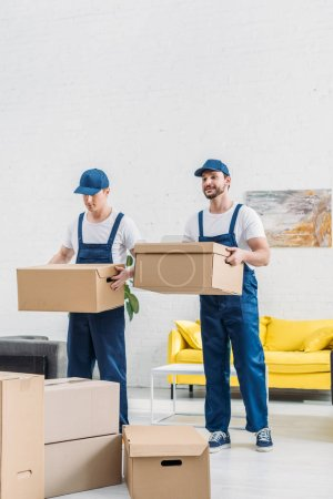 Photo for Two movers in uniform transporting cardboard boxes in apartment - Royalty Free Image
