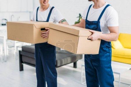 Photo pour Vue recadrée de deux déménageurs transportant des boîtes en carton dans l'appartement - image libre de droit