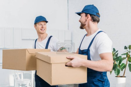 Photo for Two smiling movers transporting cardboard boxes in apartment - Royalty Free Image
