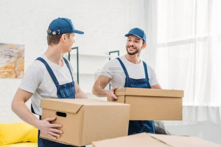 Photo for Two smiling movers looking at each other while transporting cardboard boxes in apartment - Royalty Free Image