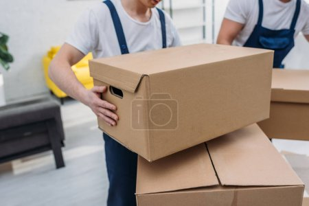 Photo for Cropped view of two movers transporting cardboard boxes in apartment - Royalty Free Image