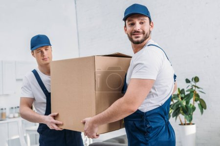 Photo for Two handsome movers transporting cardboard box in apartment - Royalty Free Image