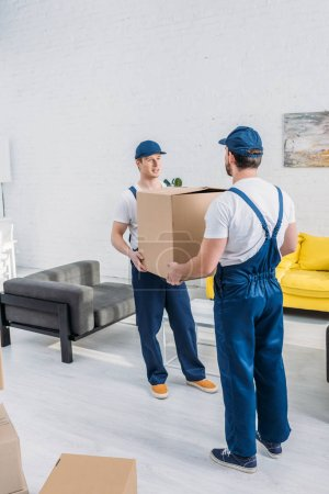 Photo for Two movers in uniform transporting cardboard box in living room - Royalty Free Image