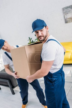 two movers in uniform transporting cardboard box in apartment