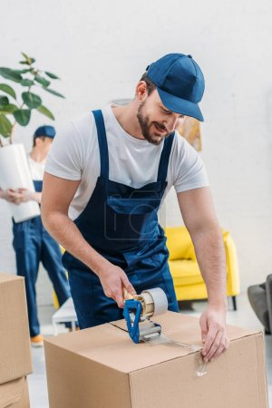 Photo for Handsome mover in uniform wrapping cardboard box with scotch tape in apartment - Royalty Free Image
