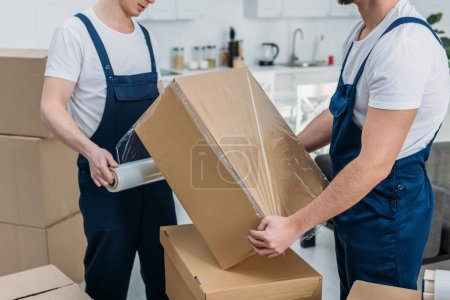 Photo for Partial view of movers wrapping cardboard box with stretch film in apartment - Royalty Free Image