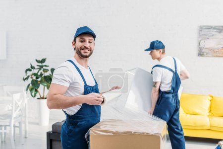 Photo for Handsome mover in uniform looking at camera while wrapping cardboard box with stretch film in apartment - Royalty Free Image
