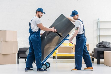Photo for Two movers using hand truck while transporting refrigerator in living room - Royalty Free Image