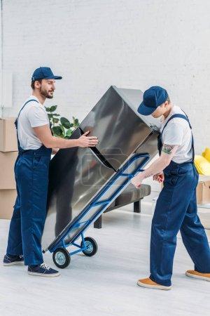 Photo pour Deux déménageurs utilisant camion à main lors du transport réfrigérateur dans l'appartement - image libre de droit