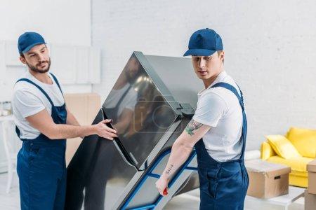 Foto de Dos motores en uniforme usando el camión de mano mientras transporta el refrigerador en el apartamento - Imagen libre de derechos