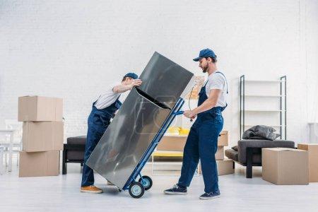 Photo pour Deux déménageurs en uniforme utilisant camion à main lors du transport réfrigérateur dans l'appartement - image libre de droit