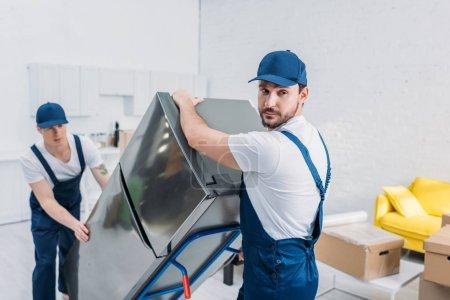 Foto de Dos guapos motores con camión de mano mientras transportan el refrigerador en el apartamento - Imagen libre de derechos