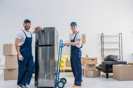 Photo pour Deux déménageurs souriants utilisant camion à main lors du transport réfrigérateur dans l'appartement - image libre de droit