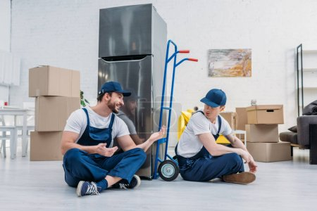 Photo for Two movers talking while sitting near hand truck, carboard boxes and refrigerator in apartment - Royalty Free Image