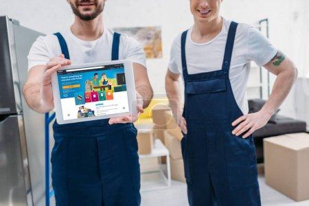 Photo pour Vue recadrée de deux déménageurs présentant la tablette numérique avec l'application Amazon sur l'écran dans l'appartement - image libre de droit