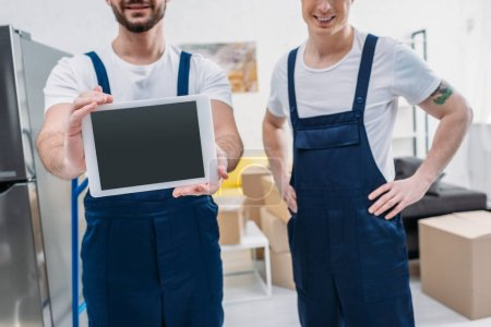 Photo for Cropped view of two movers presenting digital tablet with blank screen in apartment - Royalty Free Image
