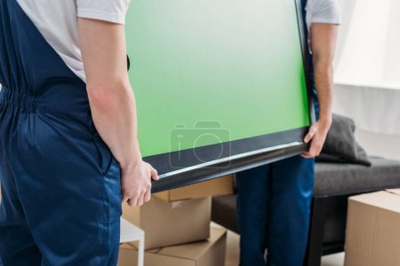 Photo for Cropped view of two movers in uniform transporting tv with green screen in apartment - Royalty Free Image