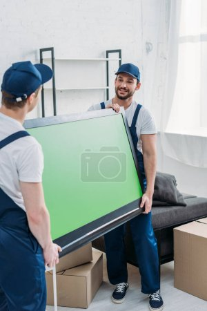 two movers transporting tv with green screen in apartment