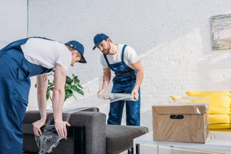 Photo pour Déménageurs emballage canapé avec rouleau de film extensible dans l'appartement avec l'espace de copie - image libre de droit