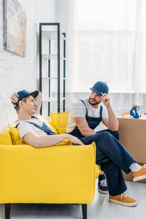 Photo for Two movers in uniform sitting on couch in apartment - Royalty Free Image