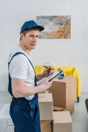 Photo for Handsome mover holding clipboard and looking at camera near cardboard boxes in apartment - Royalty Free Image