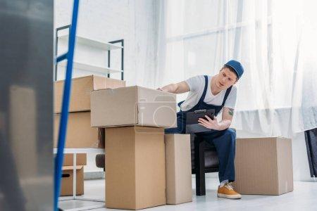 Foto de Mover sentado cerca de cajas de cartón y sosteniendo el portapapeles en el apartamento - Imagen libre de derechos