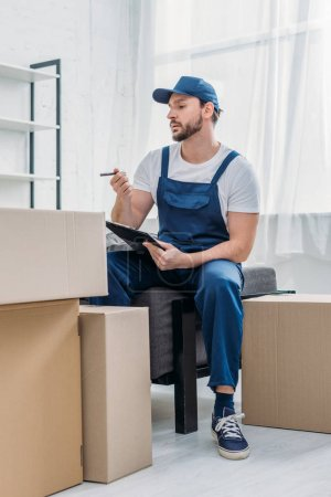 Photo for Handsome mover sitting near cardboard boxes and holding clipboard in apartment - Royalty Free Image