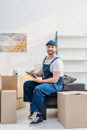 Photo for Mover in uniform looking at camera while sitting near cardboard boxes with clipboard in apartment - Royalty Free Image