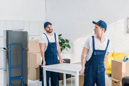 Photo pour Deux déménageurs en uniforme table de transport dans l'appartement - image libre de droit