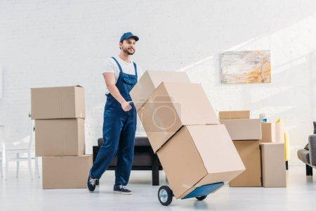 Photo pour Déménageur en uniforme transportant des boîtes en carton sur camion à main dans l'appartement - image libre de droit