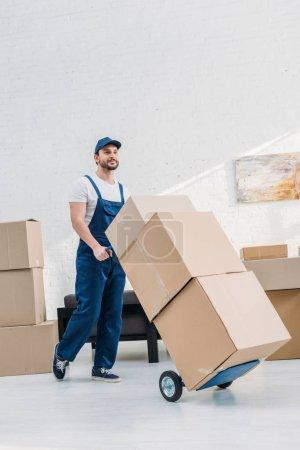 Photo pour Déménageur en uniforme transportant des boîtes en carton sur camion à main dans l'appartement avec espace de copie - image libre de droit
