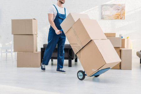 Photo for Cropped view of mover in uniform transporting cardboard boxes on hand truck in apartment - Royalty Free Image