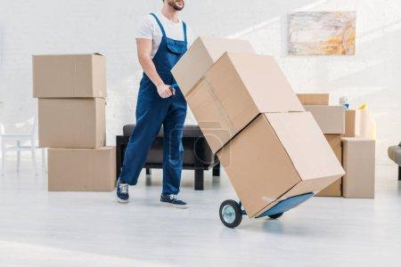 Photo pour Vue recadrée du déménageur en uniforme transportant des boîtes en carton sur camion à main dans l'appartement - image libre de droit