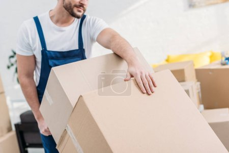 Photo for Cropped view of mover in uniform transporting cardboard boxes in apartment - Royalty Free Image
