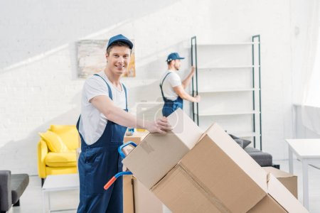 Photo for Two movers in uniform transporting cardboard boxes and furniture in apartment - Royalty Free Image