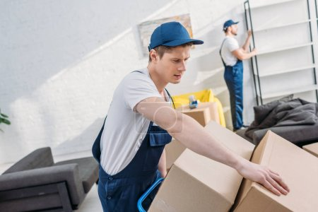 two movers transporting cardboard boxes and furniture in apartment with copy space
