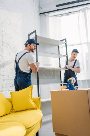 Photo for Two movers in uniform transporting rack in apartment - Royalty Free Image