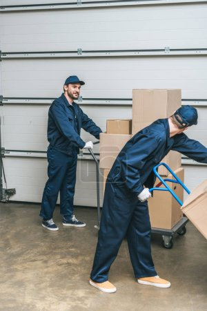 Photo for Two movers in uniform using hand trucks while transporting cardboard boxes in warehouse - Royalty Free Image