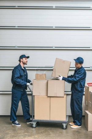 Photo for Two movers in uniform transporting cardboard boxes on hand truck in warehouse with copy space - Royalty Free Image