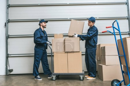 two movers in uniform transporting cardboard boxes on hand truck in warehouse with copy space