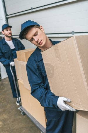 Photo for Two handsome movers in uniform transporting cardboard boxes with hand truck in warehouse - Royalty Free Image