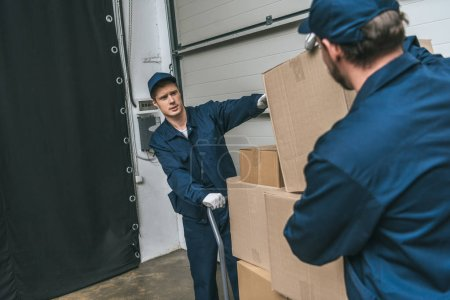 Photo for Two movers in uniform using hand truck while transporting cardboard boxes in warehouse with copy space - Royalty Free Image