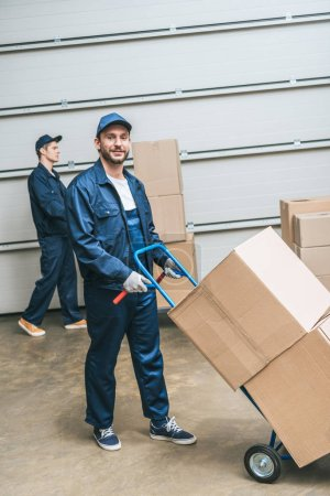 Photo for Two movers in uniform transporting cardboard boxes with hand truck in warehouse - Royalty Free Image