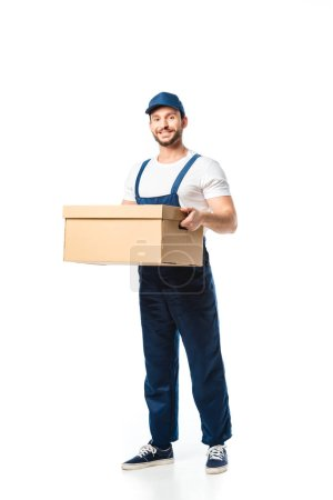 Photo for Handsome mover in uniform carrying cardboard box, smiling and looking at camera isolated on white - Royalty Free Image