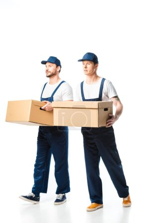 Photo for Two handsome movers in uniform transporting cardboard boxes on white - Royalty Free Image