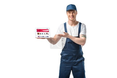 Photo for Handsome smiling mover gesturing with hand while presenting digital tablet with ebay app on screen isolated on white - Royalty Free Image