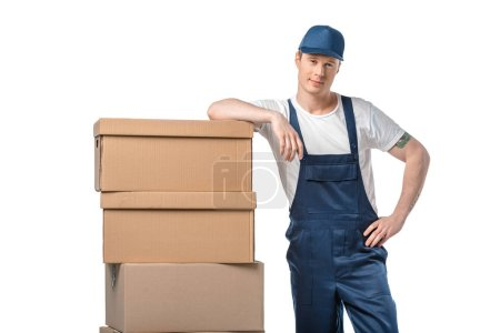 Photo for Handsome mover in uniform with cardboard boxes looking at camera isolated on white - Royalty Free Image